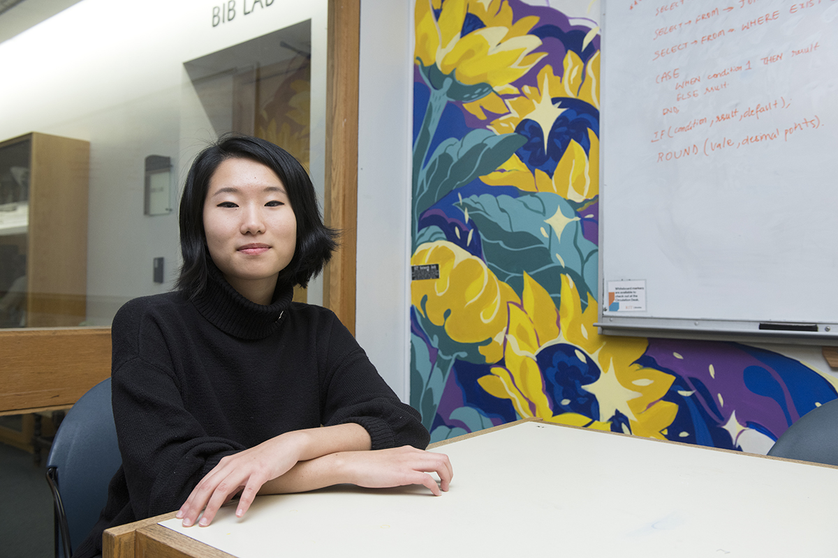 Juho Choi poses in front of the library mural she painted.