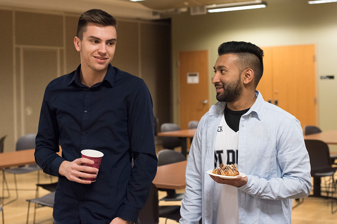 Two male students stand near each other holding refreshments