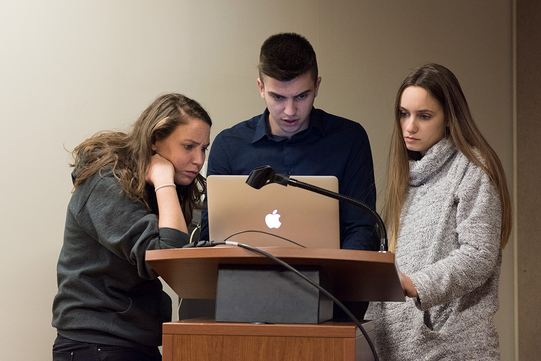 Three student standing at podium looking at laptop