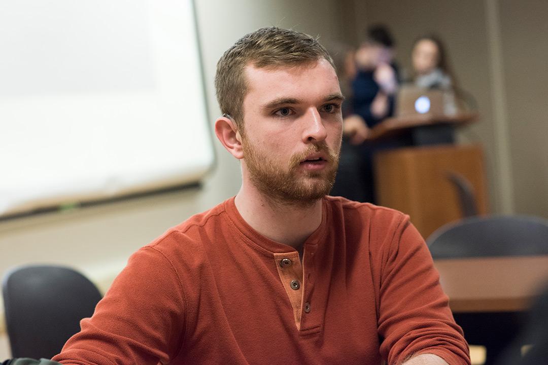 Male student wearing orange sweater