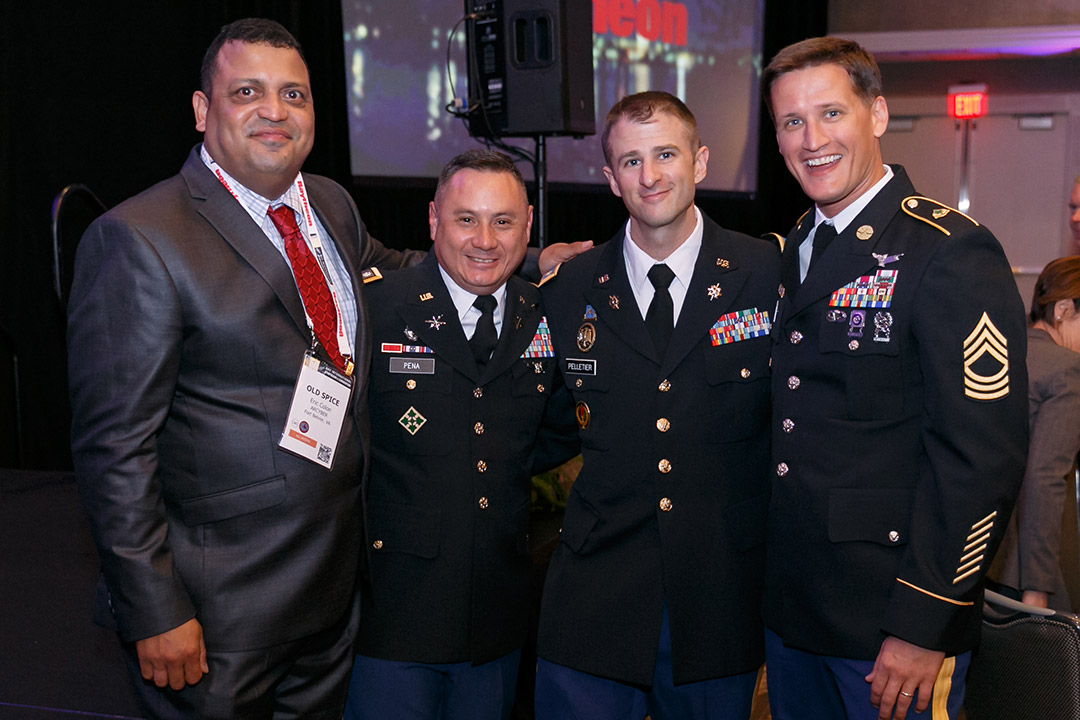 Man in suit and three men in U.S. military Class A uniforms.