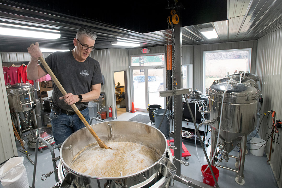man stirring large vat of beer.