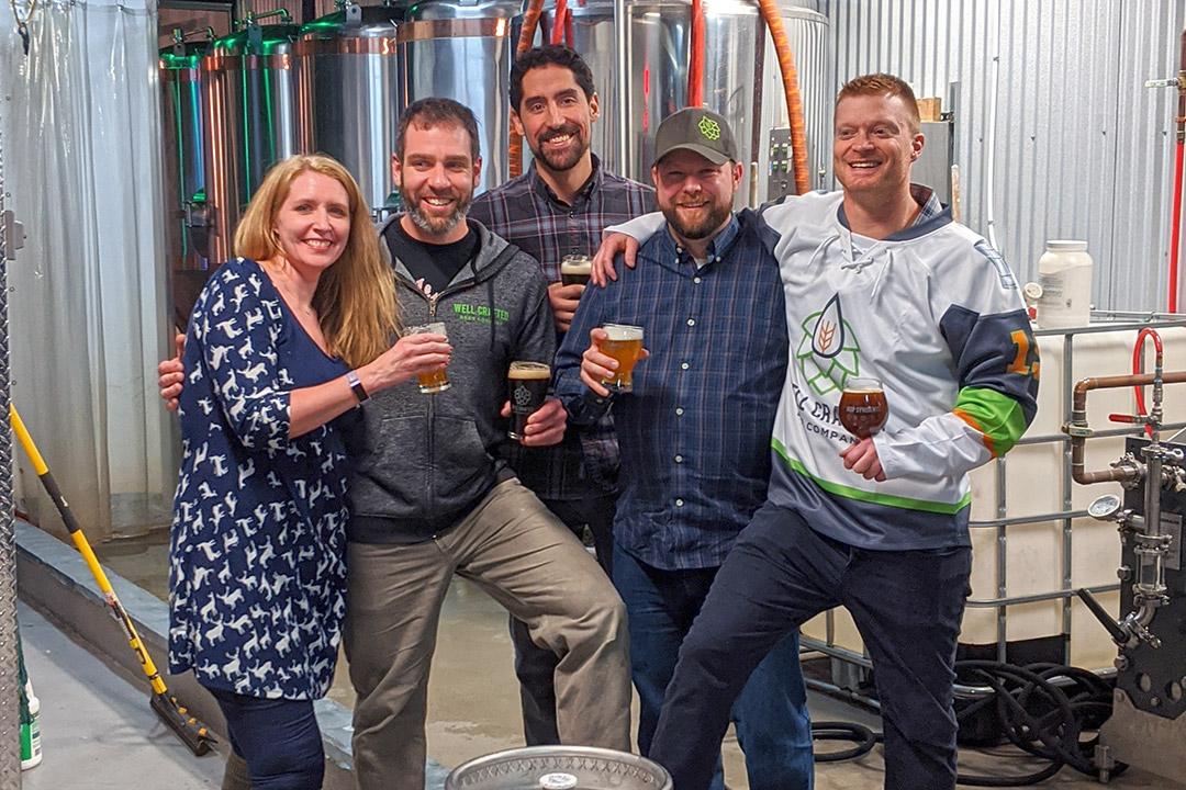 five people standing holding beers.
