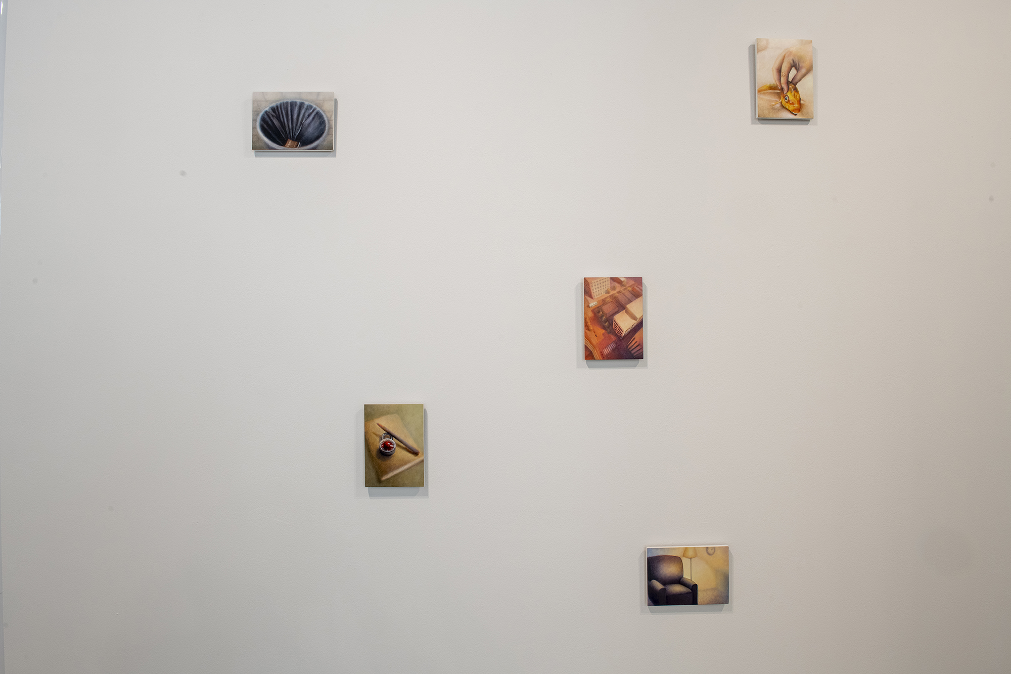A series of small paintings on a wall.