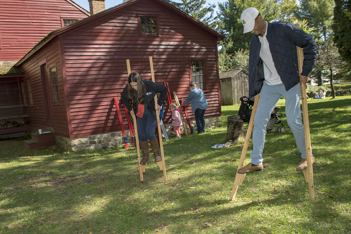 Two RIT students walk on stilts at the Genesee Country Village and Museum's annual fall fair.