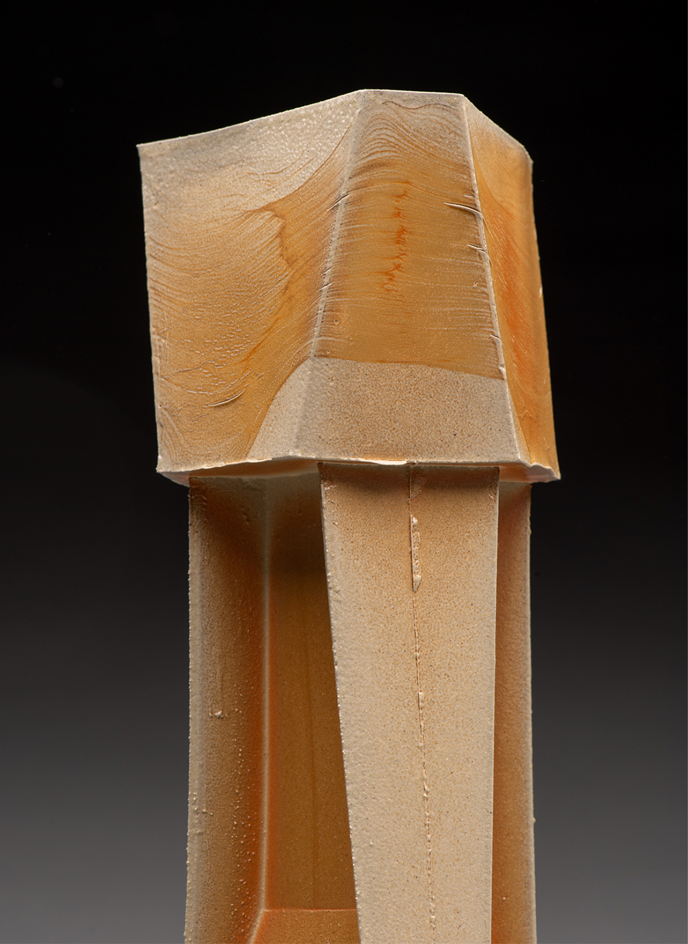 A detailed look at the top of a tall wooden sculpture inspired by industrial architecture.