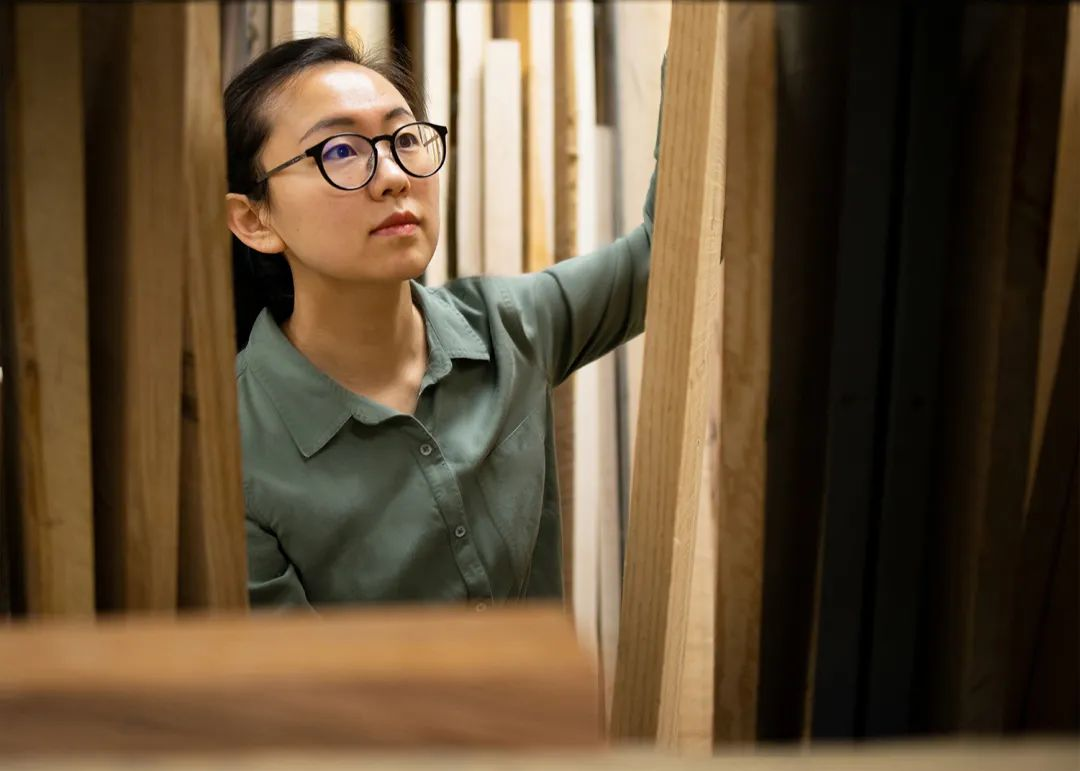 Gao Yahui surrounded by tall stack of lumber.