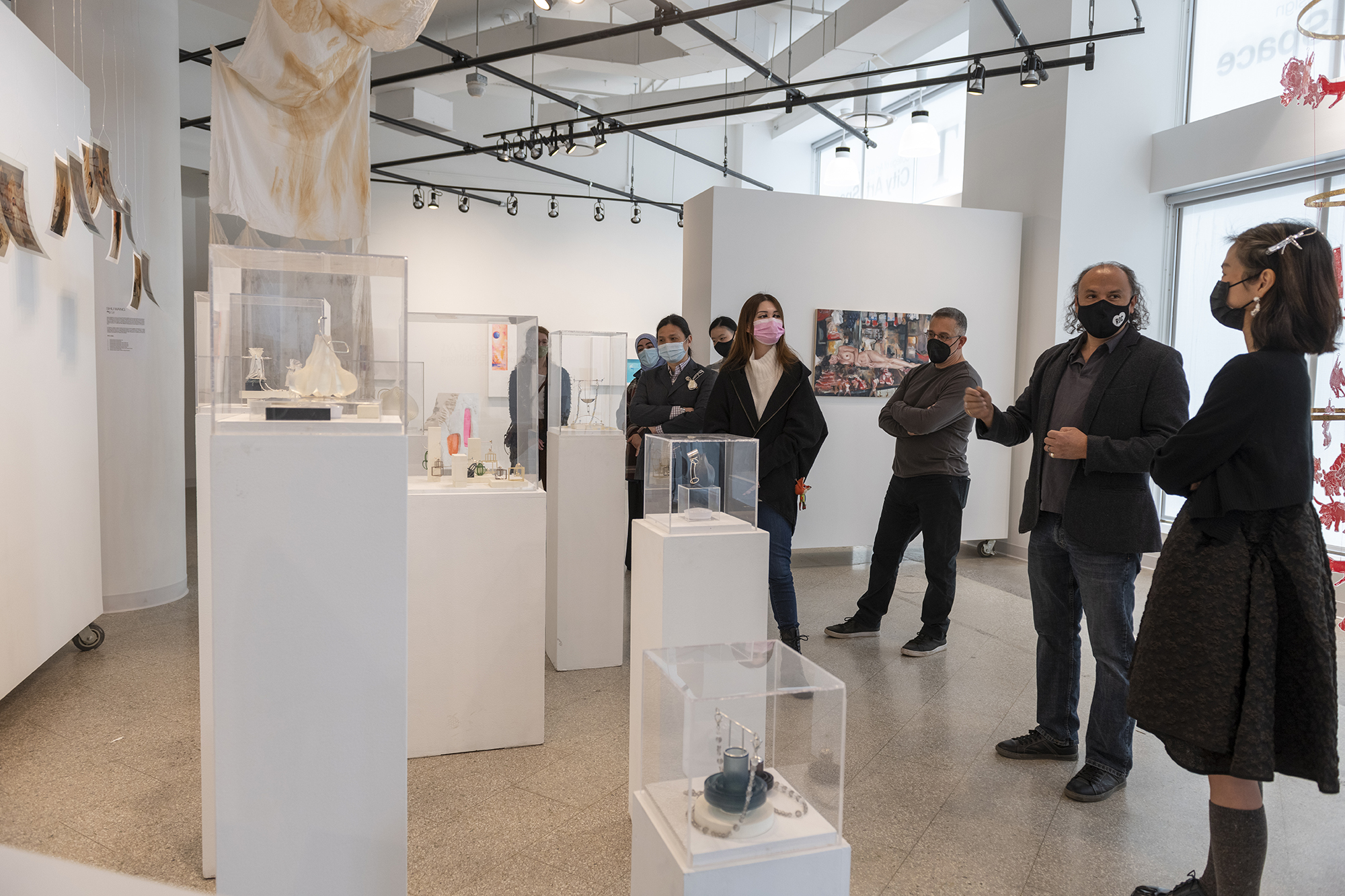 A group of people stand around an exhibit of metals and jewelry design.