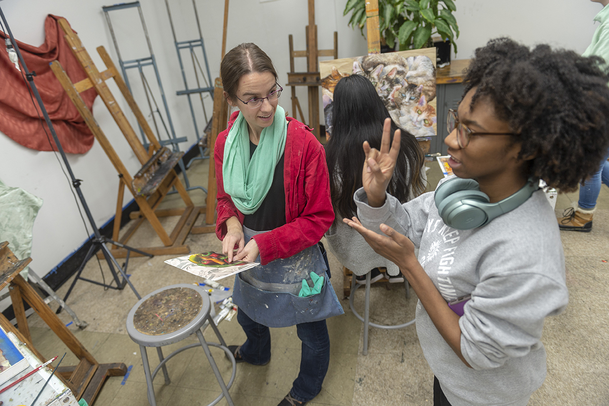 Faculty Emily Glass discusses an in-process painting with a student.