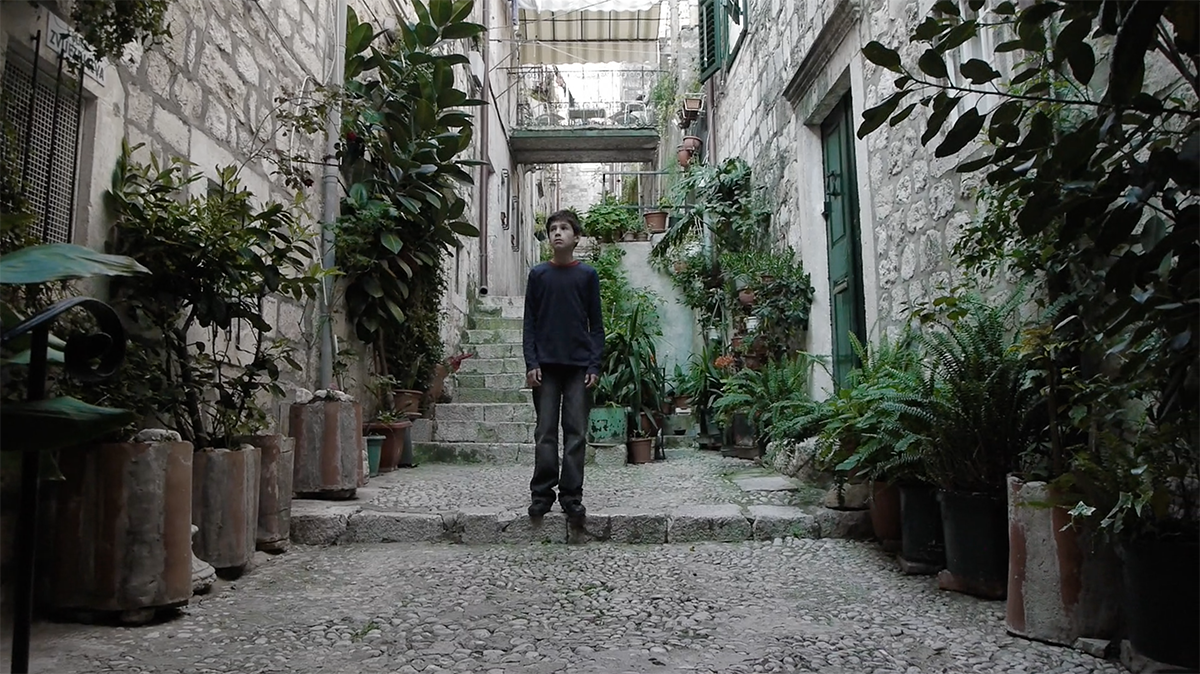 A film still of a young boy in an alley surrounded by plants.