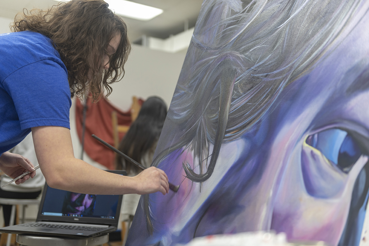 A student adds to a large painting of a vibrant purple-and-blue face.