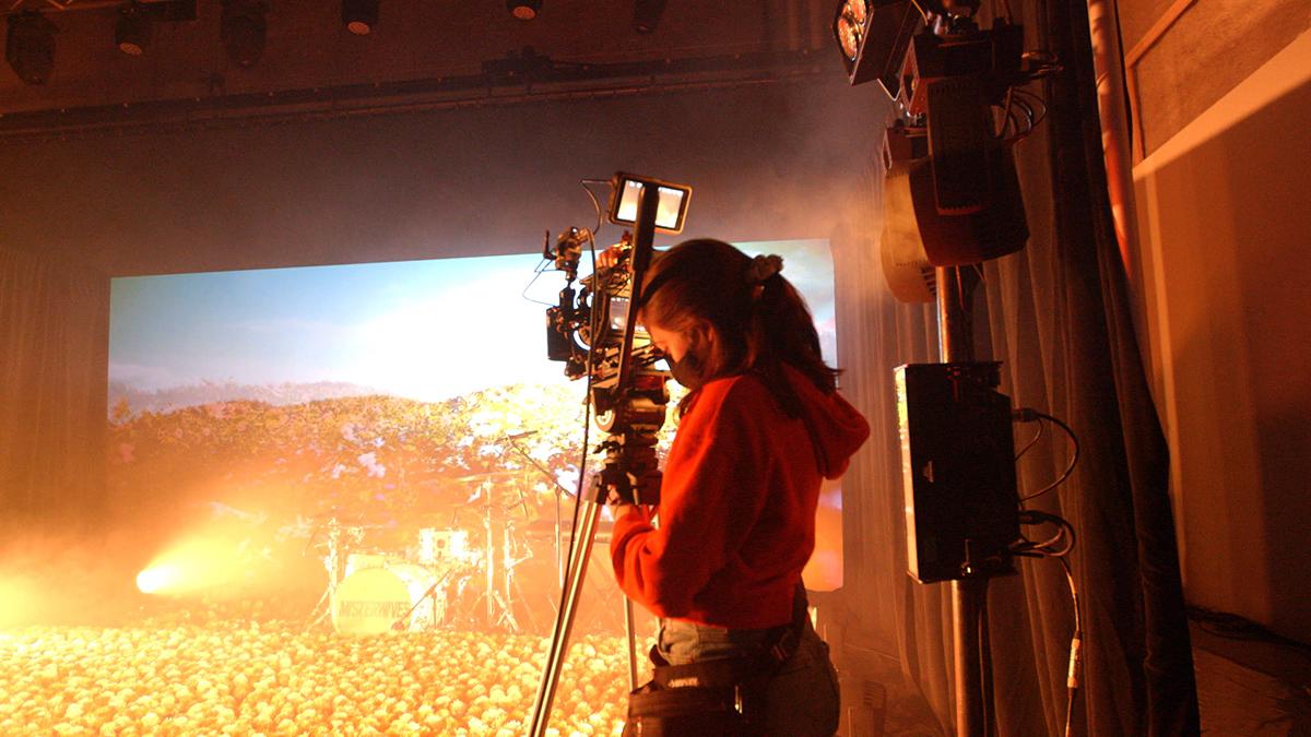 Sarah Alexander operates a camera on a production set.