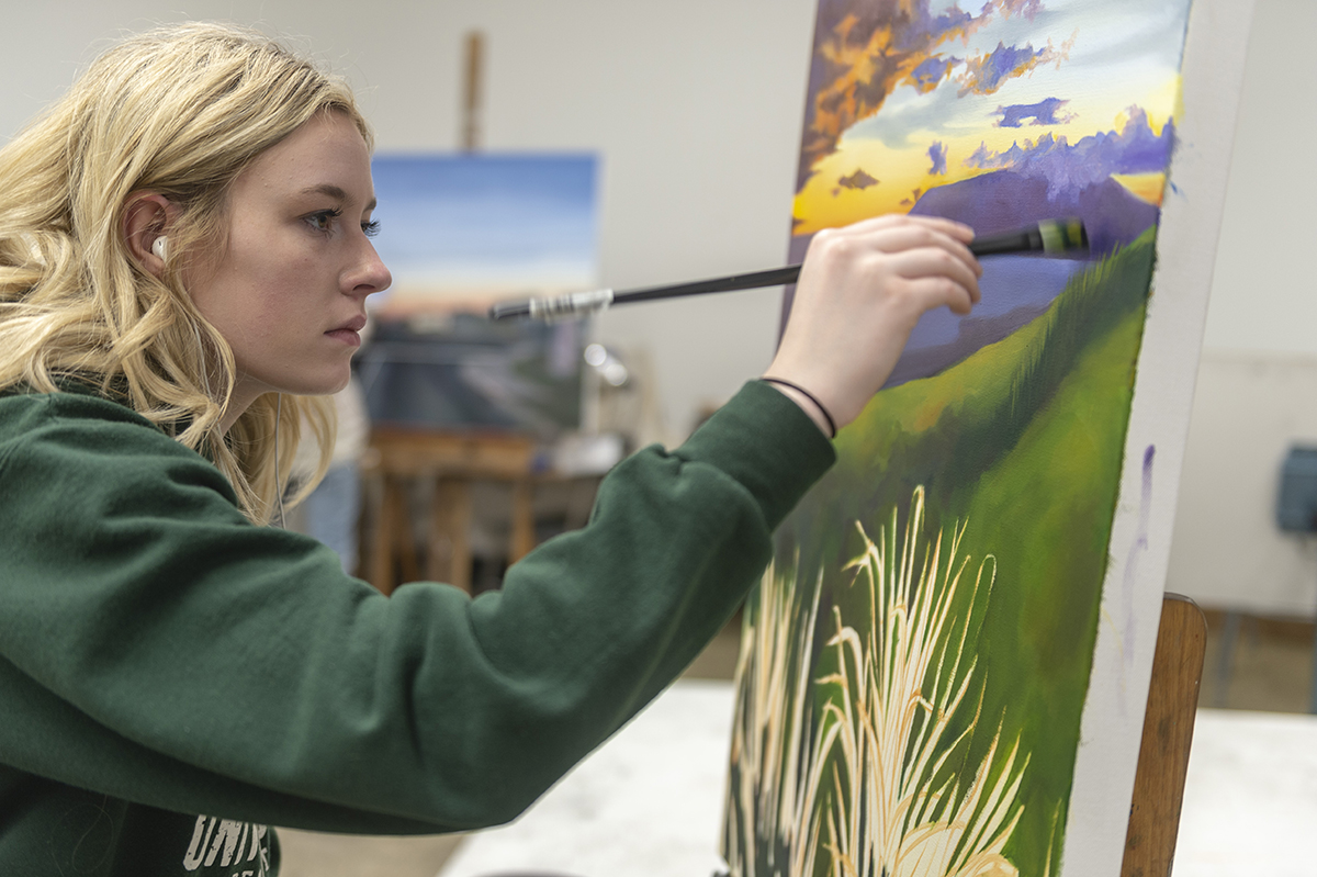 A student applies a brush stroke to her nature-inspired painting.