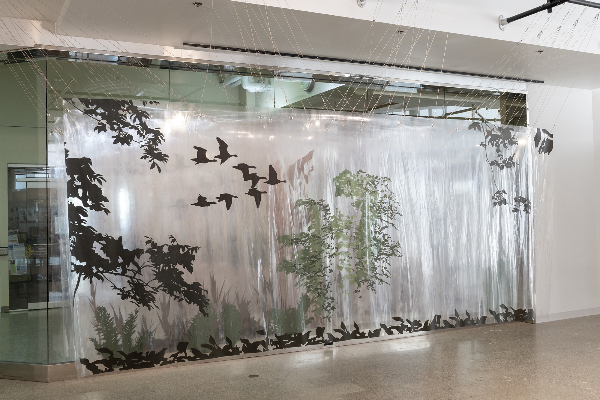 An installation piece that shows silhouettes of birds and trees.