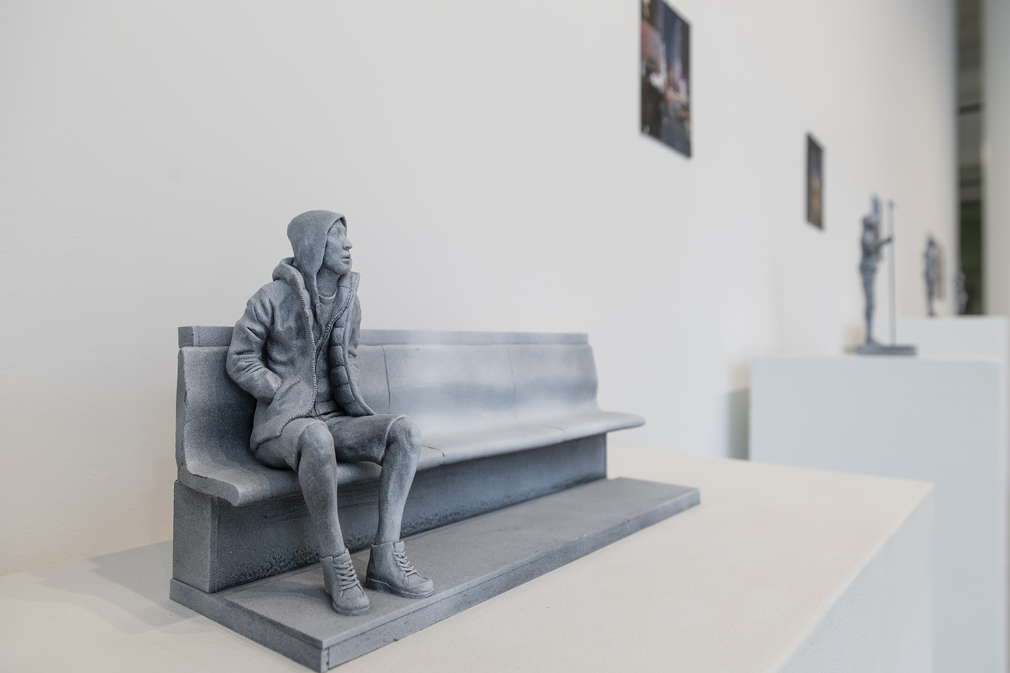 A sculpture of a person sitting on a bench.