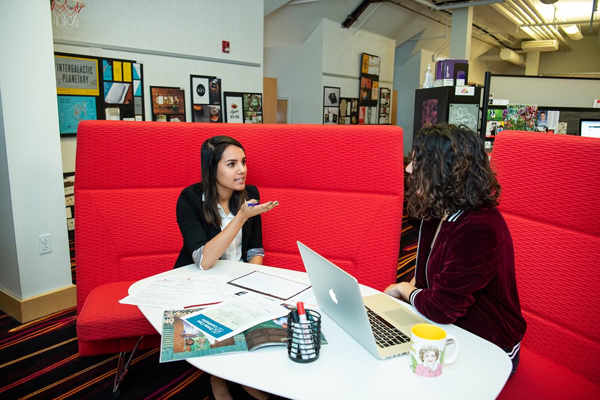 Isha Mehta and a fellow Dixon Schwabl employee talk.