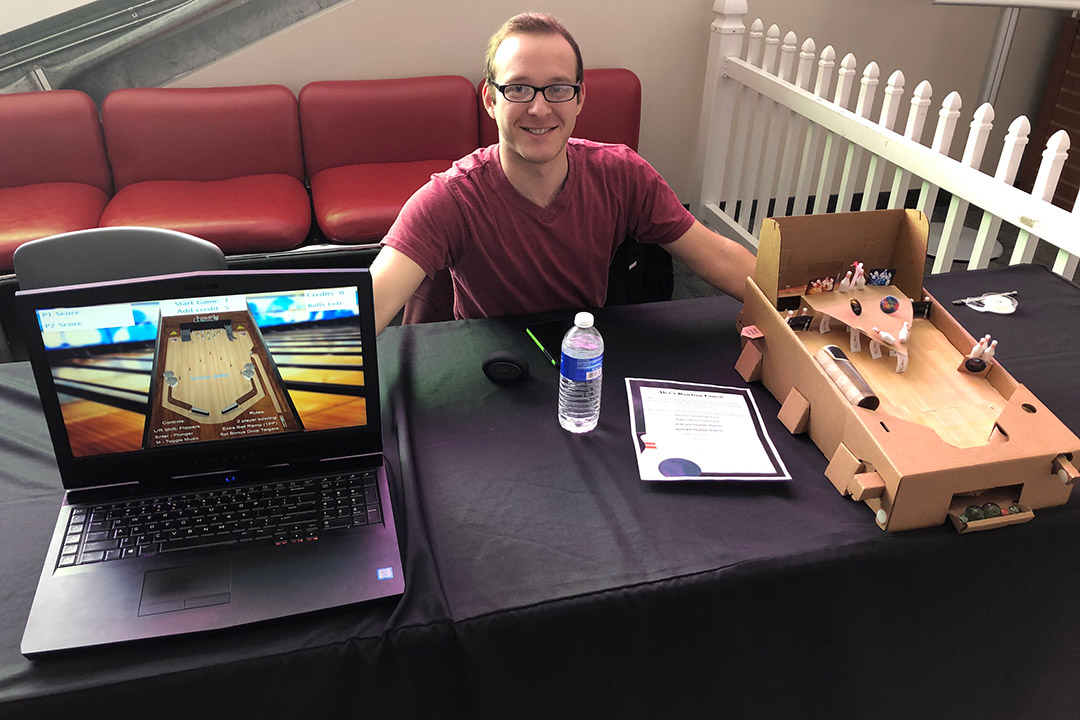 student sitting at table with cardboard prototype of pinball machine and laptop displaying virtual pinball machine.