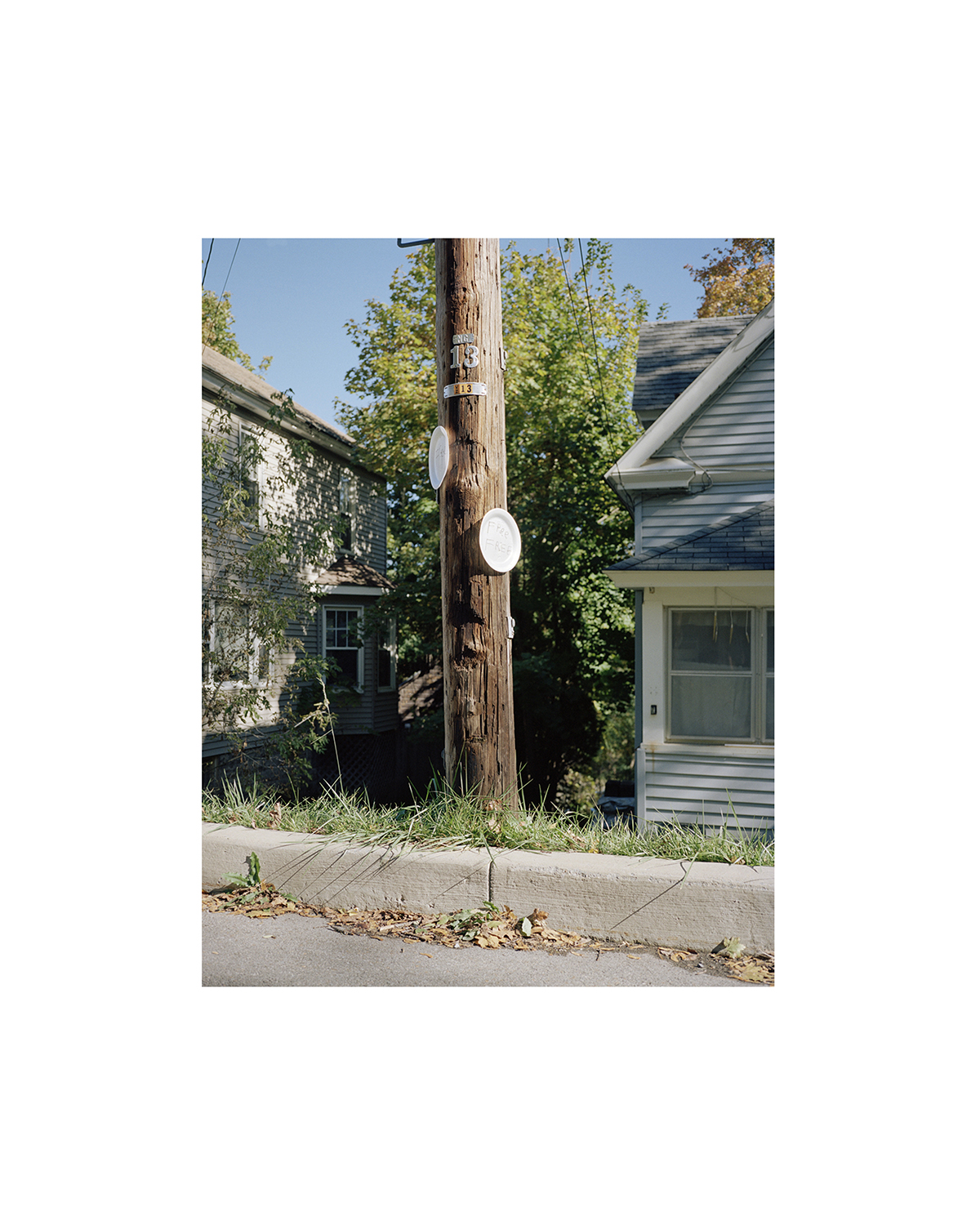 A photo of an electrical service pole between two houses.