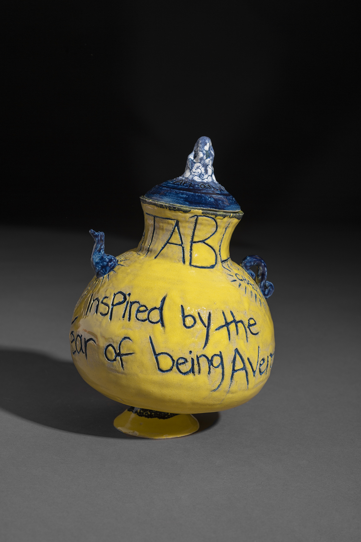 A yellow ceramic pot with blue writing on it.