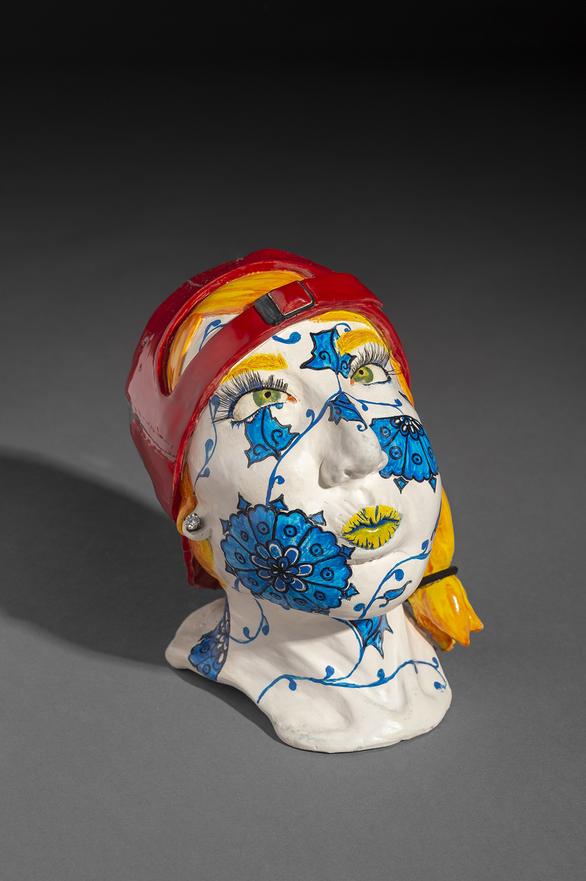 A vibrant ceramic sculpture of a face with detailed designs on it.