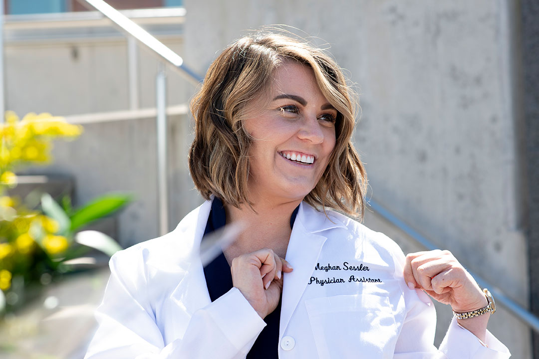 student poses for photo in her new white lab coat.
