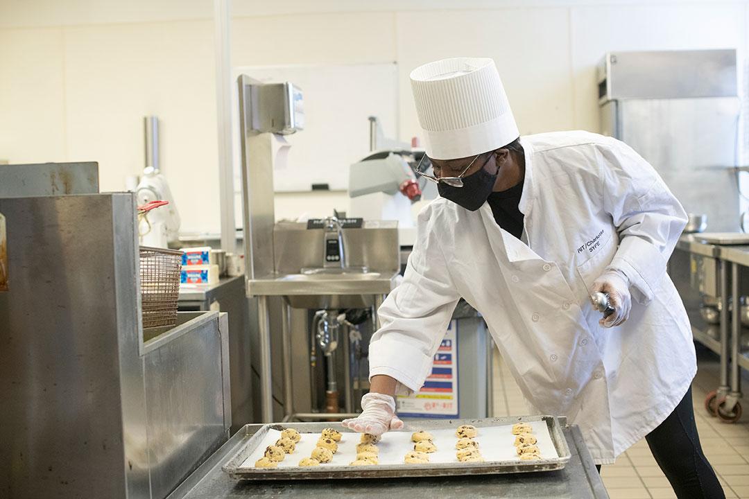 student flattening cookies on a baking sheet.