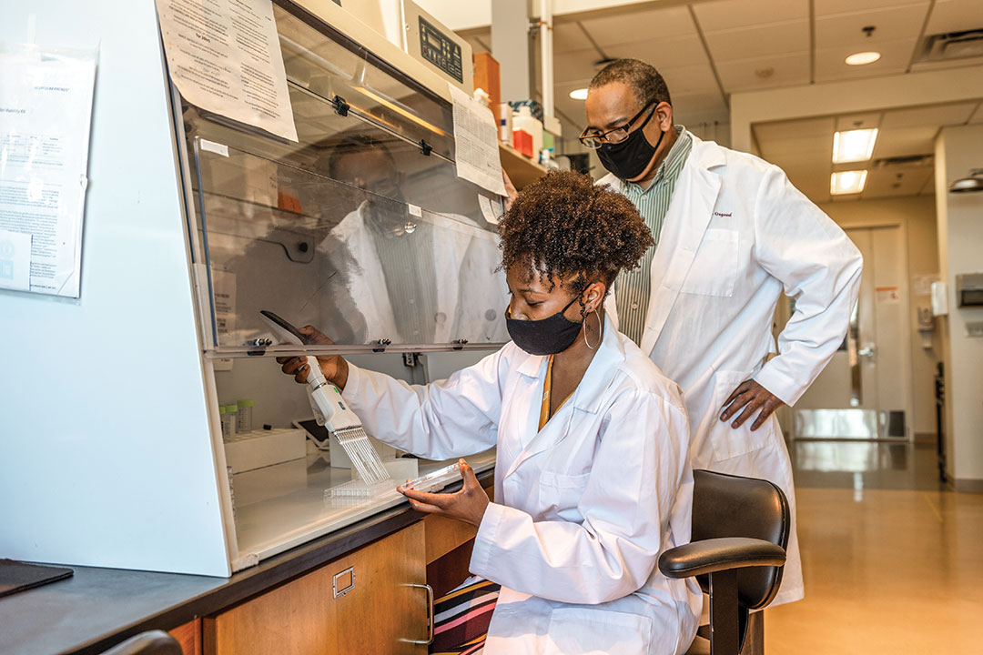 student and researcher working in a lab.