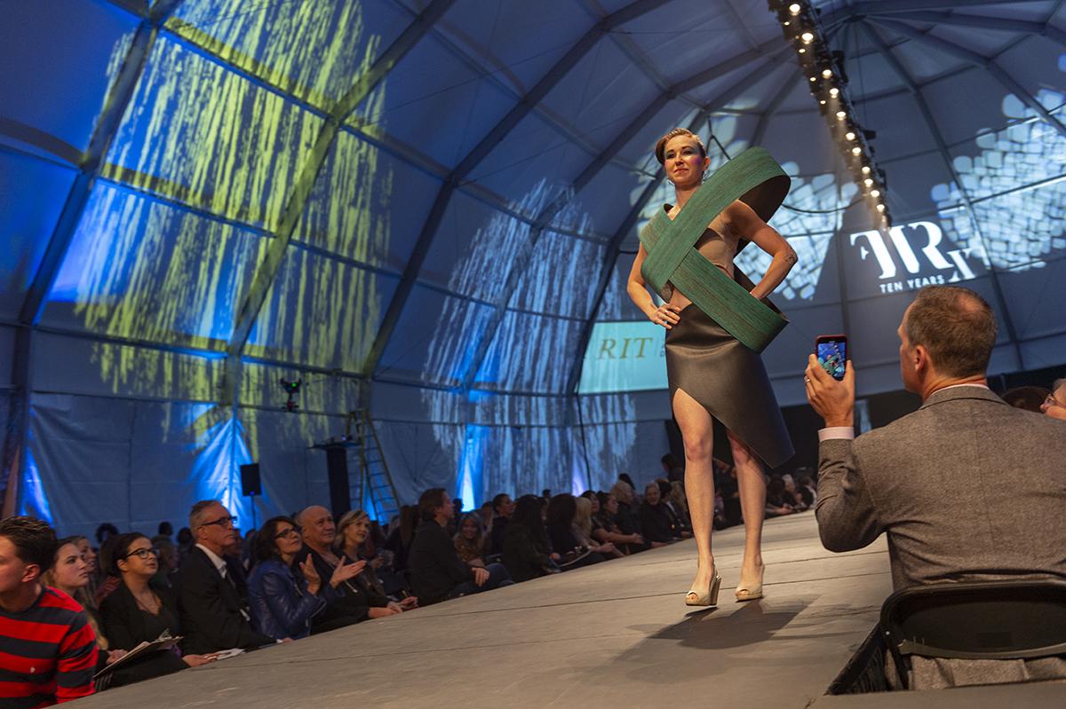 An alumna walks the runway in her wearable sculpture.