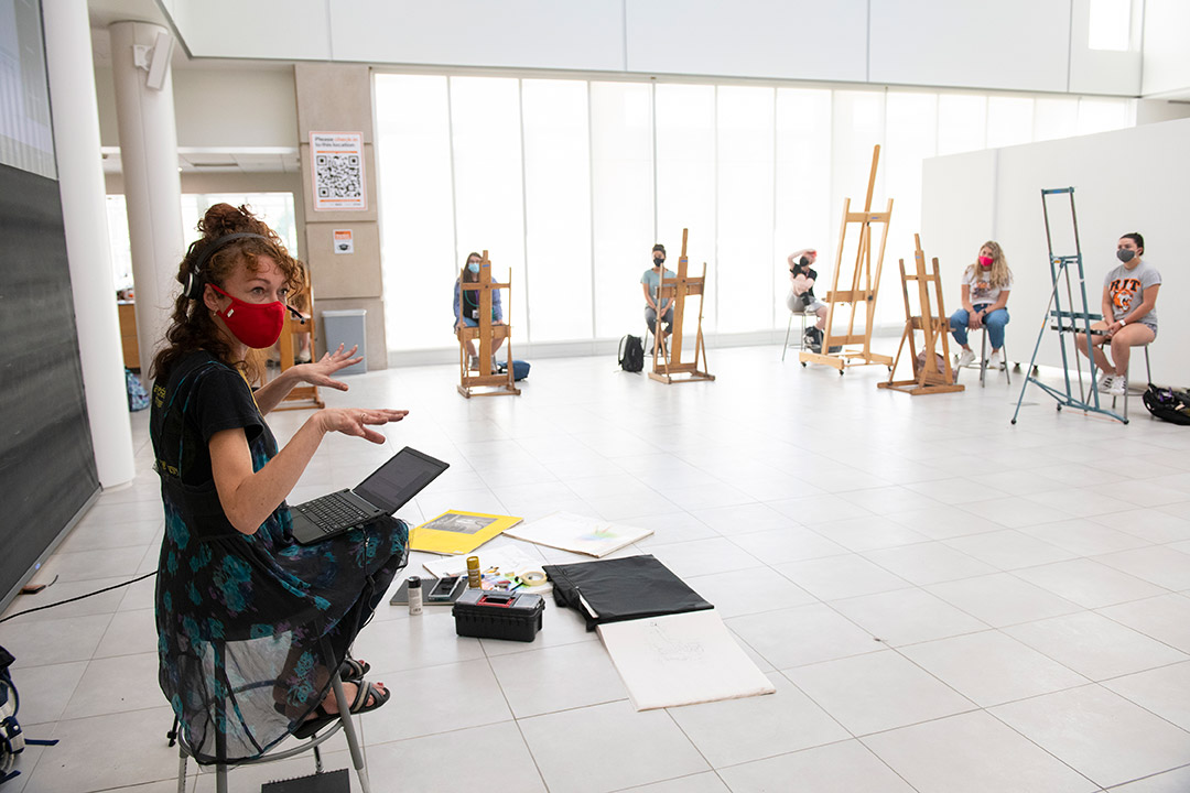 professor sitting on stool wearing mask and teaching students sitting spaced apart in gallery space.
