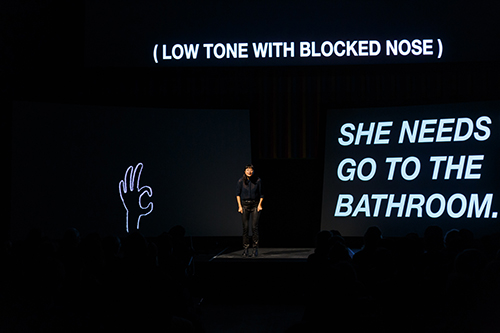 "Kim, wearing black clothes, stands on a stage, dwarfed by three large screens surrounding her. To the left, a black screen displays a hand-drawn hand with thumb and index finger forming a circle, drawn in white; above her is, in white, text reading ""(Low tone with blocked nose)""; on the right side of the image is the third screen, which reads in large white text ""She needs to go to the bathroom."""