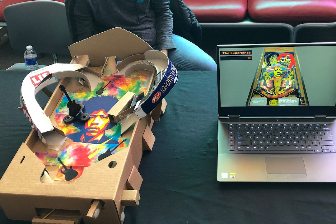 cardboard prototype of pinball machine next to laptop display of pinball machine.