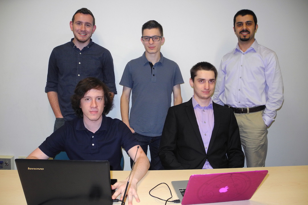 Students and professor pose around table with two computers.
