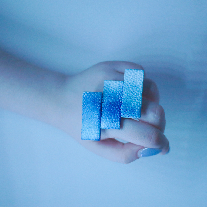 3D-printed jewelry — a blue ring with three bars.