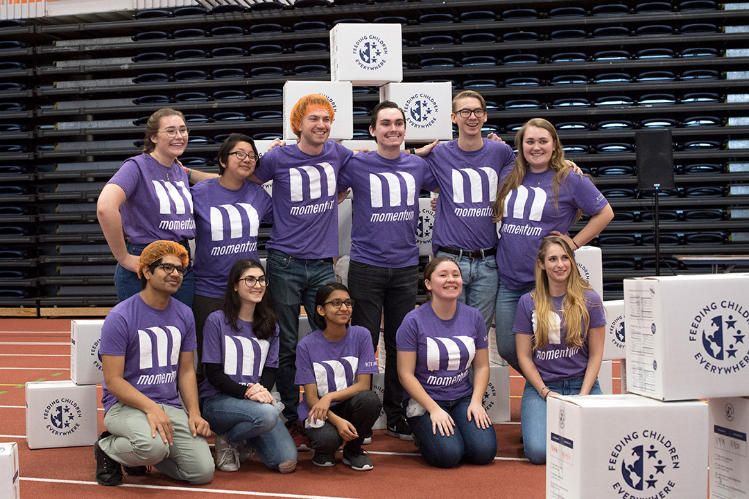 group of 11 students posing wearing purple T-shirts.
