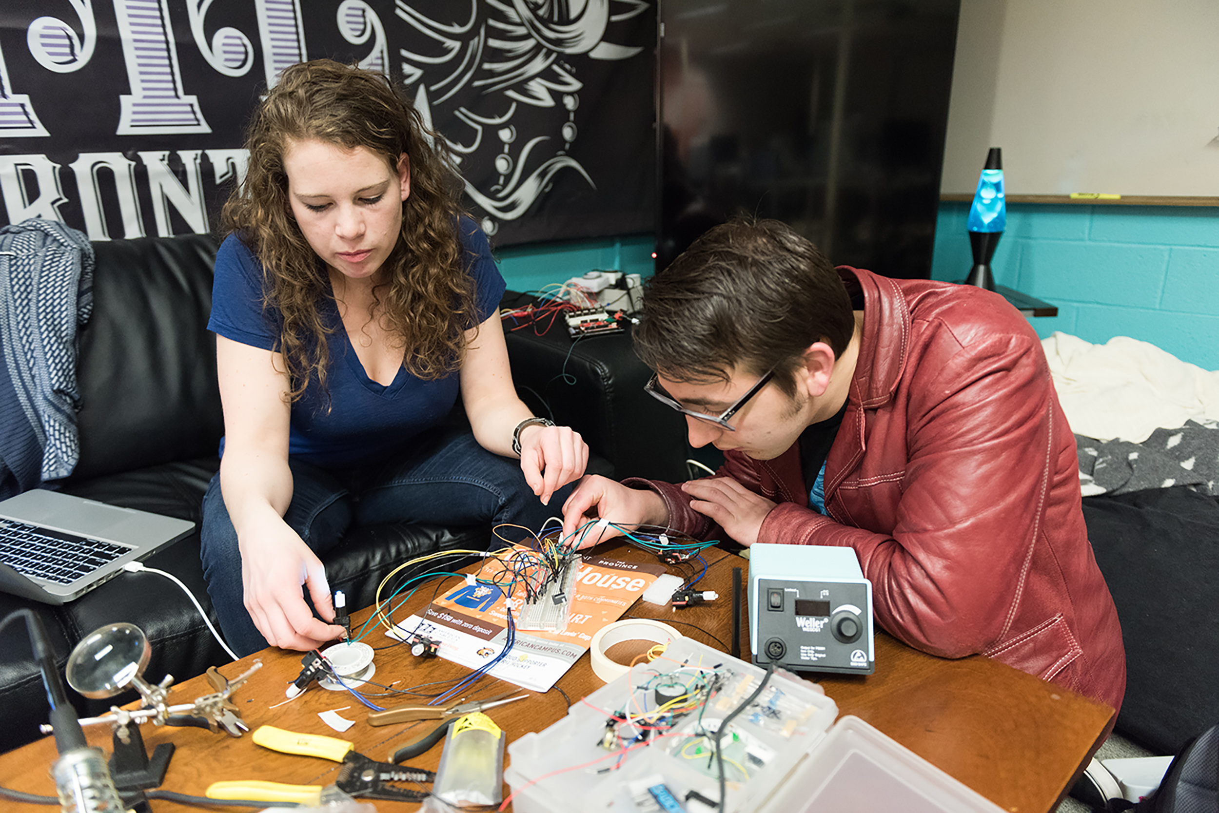 Two students sit at a table with a variety of electronics while soldering some of them