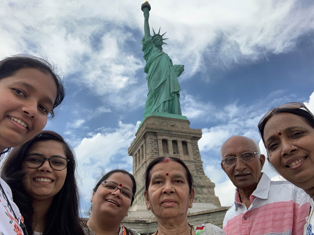 A group of people pose for a photo in front of the Statue of Liberty.