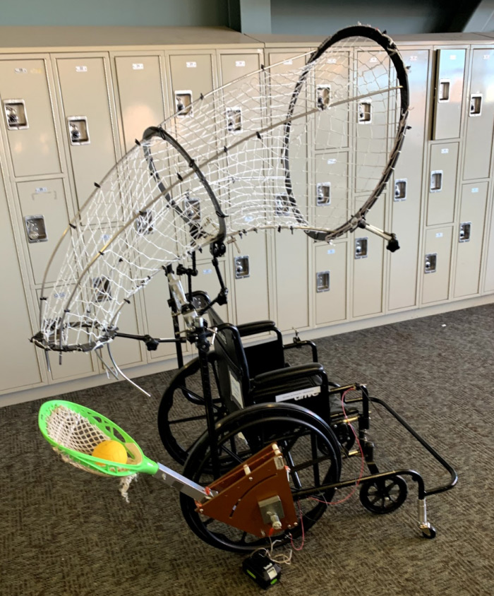 Wheelchair outfitted with a net to catch a ball and the pocket from a lacrosse stick to throw the ball.
