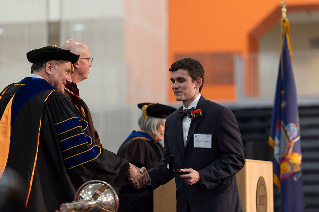 Student shakes hands with staff member dressed in regalia.