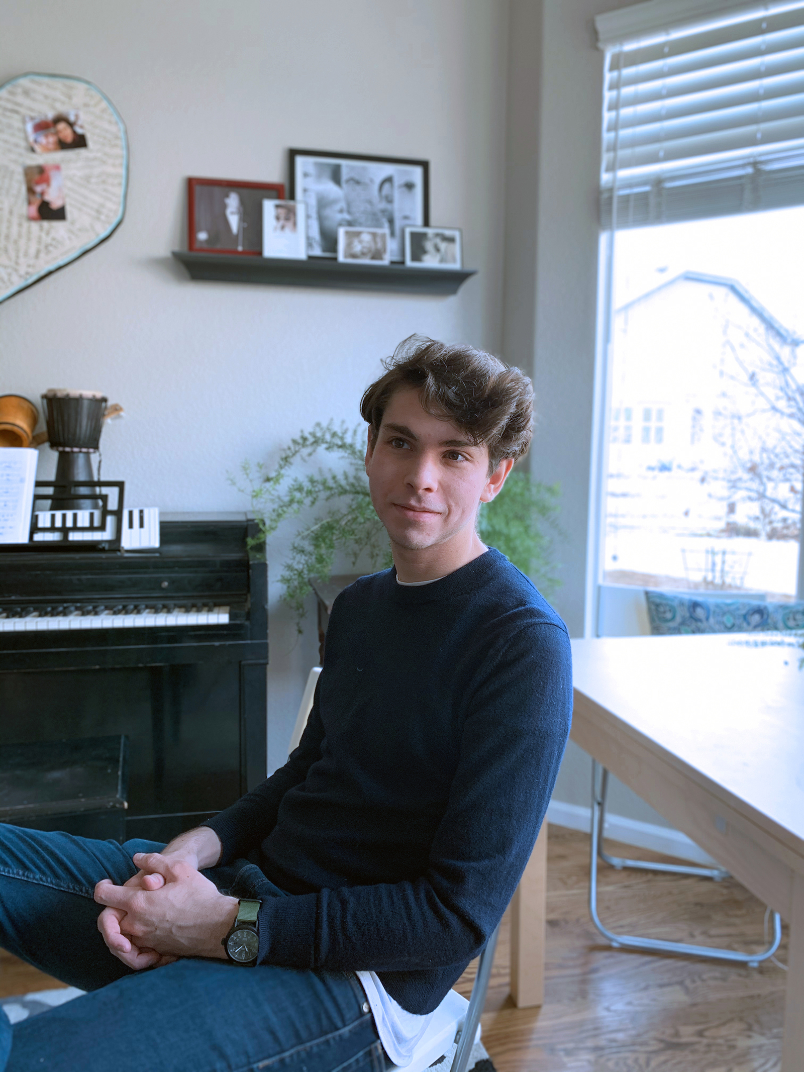 A portrait of Will McCloskey set against a window and piano.