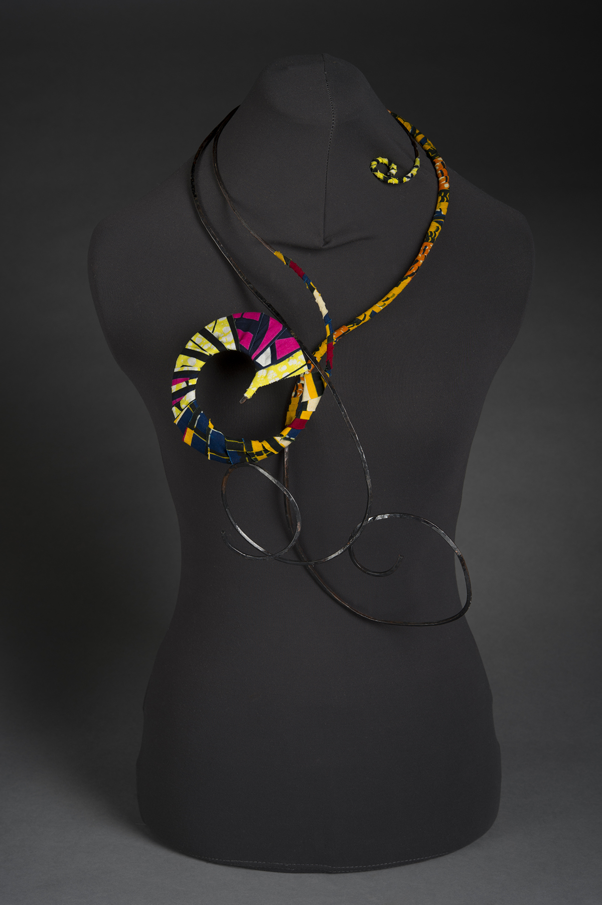 A colorful jewelry piece is displayed on a mannequin.