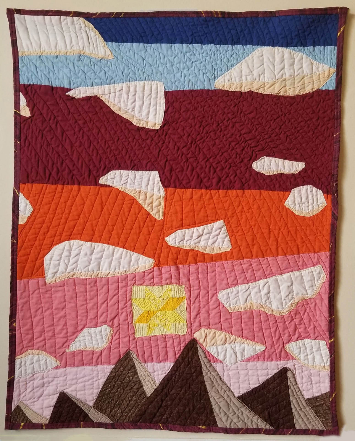 A nature quilt of the sun over mountains.