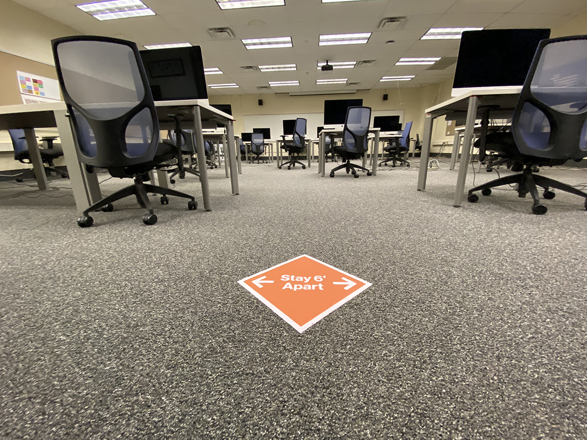 A computer lab with a sign encouraging six feet of distance.