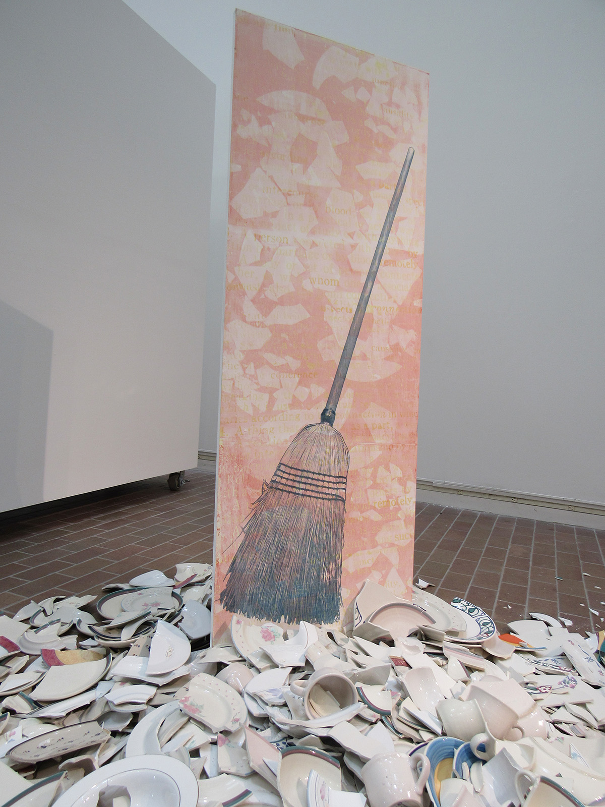 A large-scale print of a mop next to broken dishware in a gallery.