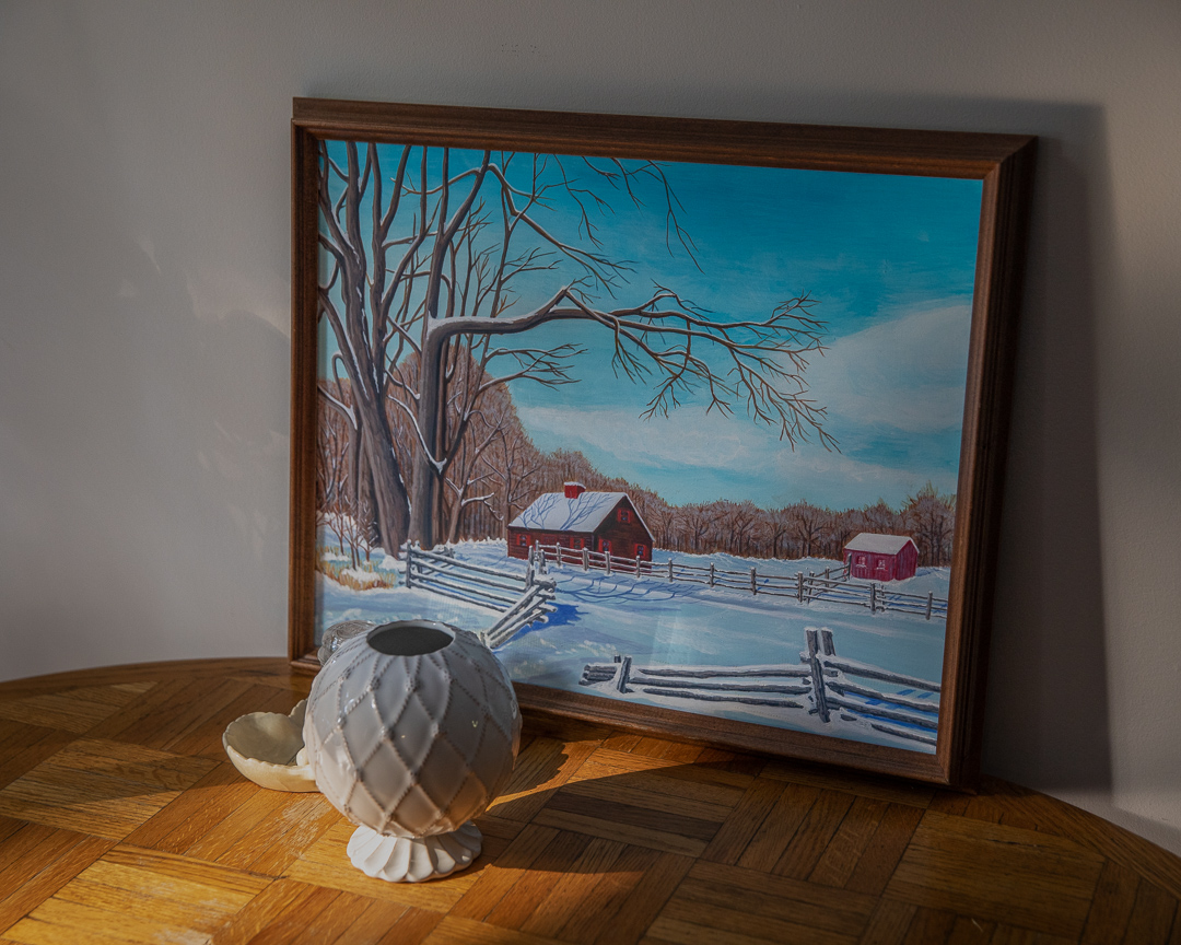 A photo of a painting of a house set against a snow scenery.