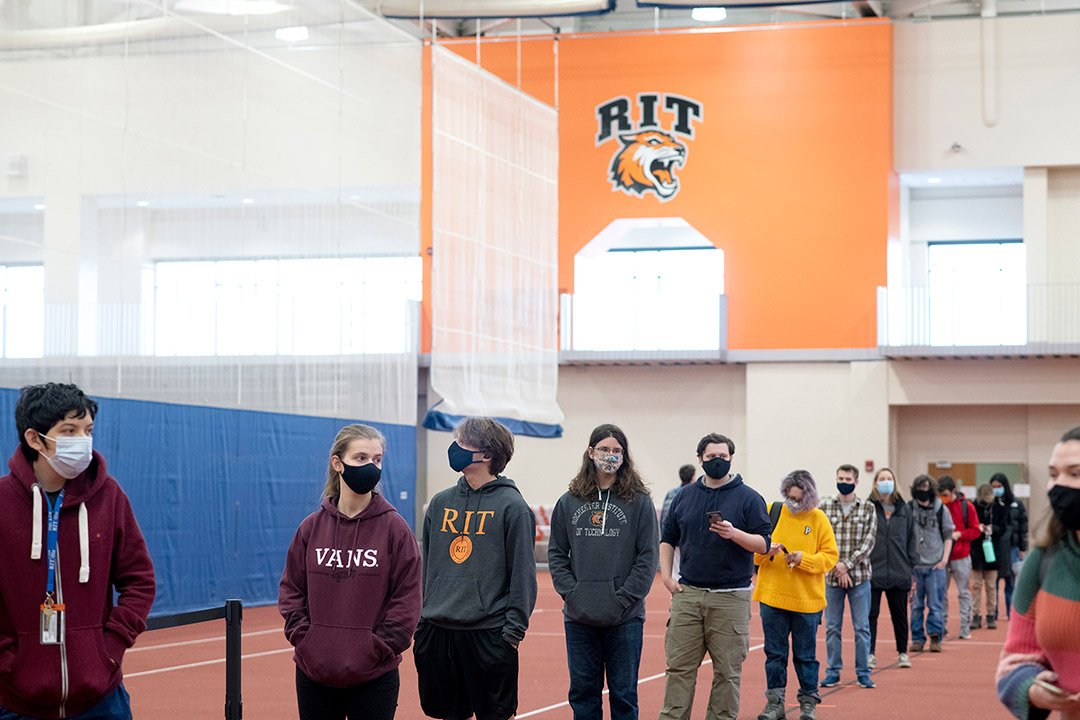 line of students wearing masks in field house.