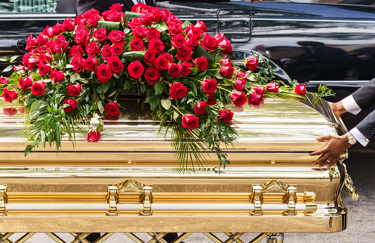 A gold-plated casket holding George Floyd is carried to a hearse at his funeral service.