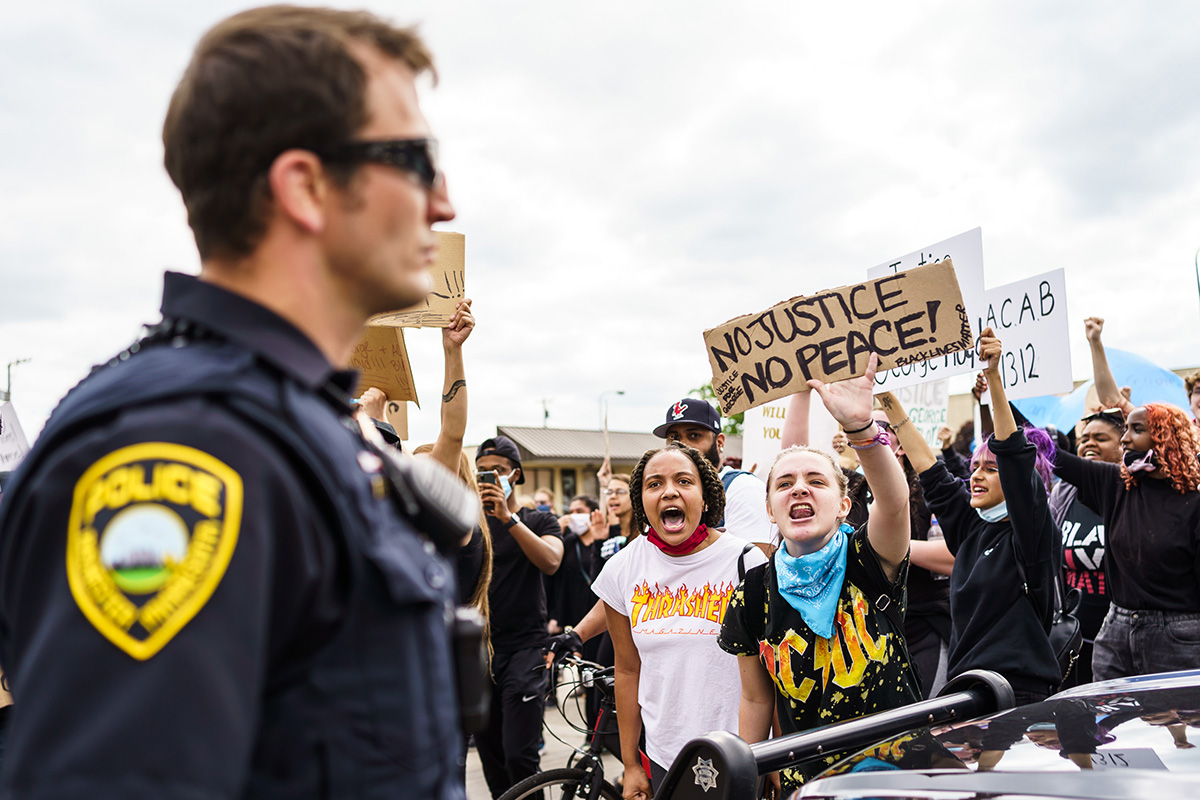 A crowd of protesters hold up signs as a police officer looks on.