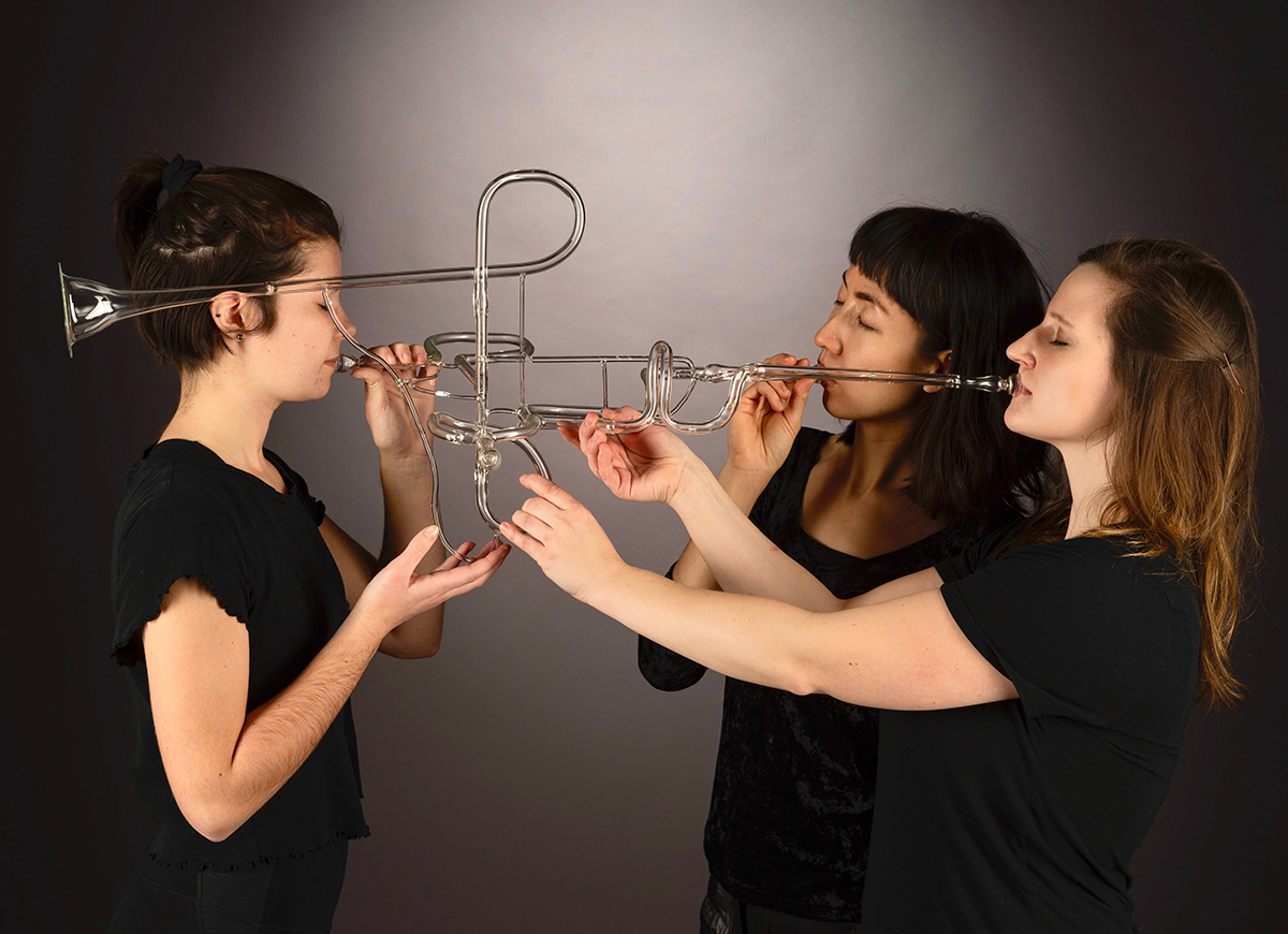 Three students blow into mouthpieces of a flameworked trumpet.