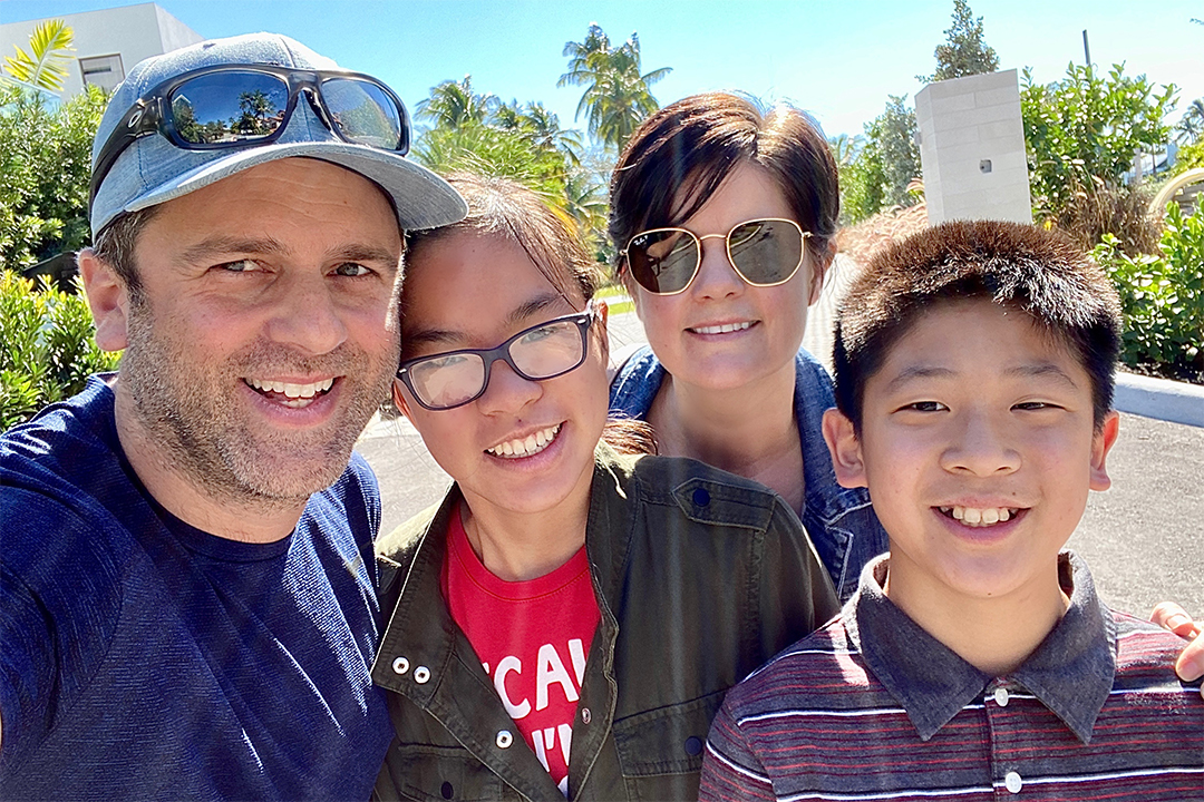 Four people outside in a sunny day smiling at the camera.