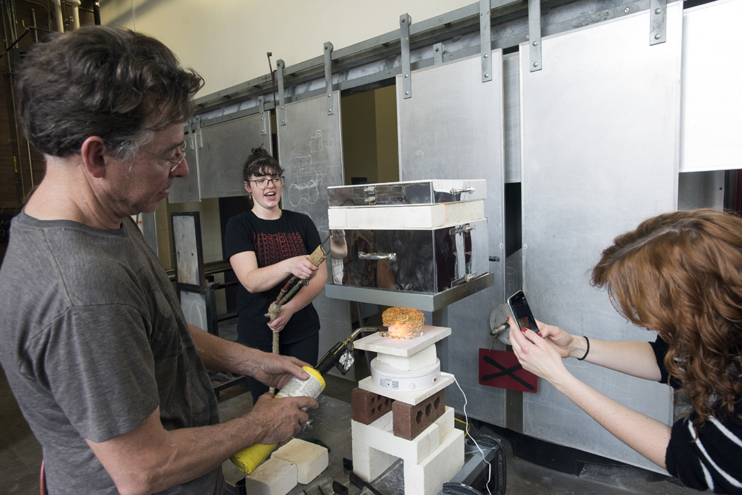 Peter Houk, middle, takes a flame to an auto-coiled object